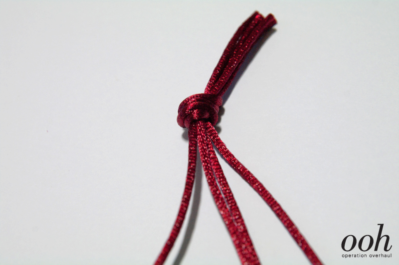 Tie strands together with knot